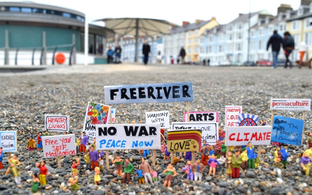"Little toy people on a pebble beach hold aloft protest signs that say: ""no war"" and ""arts"" and ""free river"". Cute and peaceful."