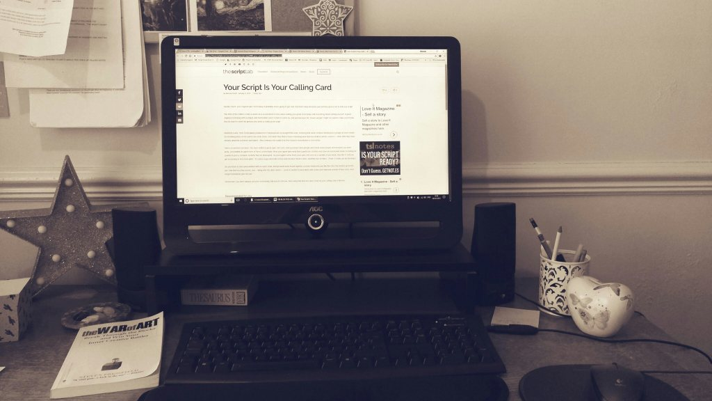 Desk, PC, paraphernalia associated with writing: pens, pen pot, book, thesaurus